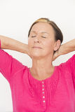 Laid back relaxed woman closed eyes. Portrait attractive mature woman with arms up and hands in neck, relaxed, happy and daydreaming with closed eyes, isolated Royalty Free Stock Images