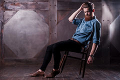 Laid-back style . Picture of a handsome young bearded man posing while sitting on chair Royalty Free Stock Photos