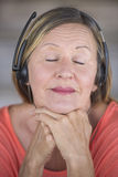 Laid back woman with headphones music listening. Portrait attractive mature woman listening happy relaxed with closed eyes to music with headphones, blurred Stock Image