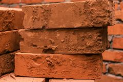 Laid on each other old, damaged, red bricks. Close-up Stock Photo