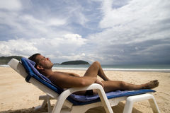Laid man. Tanned man laid on a chair at a white sand beach, Phuket Island, Thailand Royalty Free Stock Photography