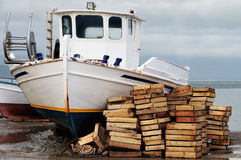Laid out fishing boat. Winter picture of a laid out fishing boat with a stack of empty wooden fish boxes next to it. Image conveys a sense of abandonment, decay Royalty Free Stock Photos