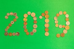 2019 is laid out of various coins on a green background. New yea