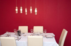 Laid and set table. Side view of place settings on laid table under modern lights with red background and copy space Stock Images
