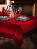 Laid table. Table prepared with red tablecloth, elegant dishes and glasses Royalty Free Stock Image