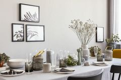 Laid table with champagne glasses and flowers in a modern dining room interior. Real photo stock images