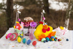 Laid table for Easter: toy chicken with colorful Easter eggs - blue, green, yellow, red - Easter cake, paper figurines of chickens. On white tablecloth Royalty Free Stock Image