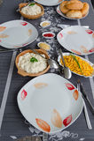 Laid Table. Finished table with red and white plates, cutlery and small dishes with side dishes to the barbecue Stock Image