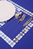 Laid table -  fork and spoon laid on blue cloth and white plate Stock Image