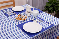 Laid table -  fork and spoon laid on blue cloth and white plate Stock Photography