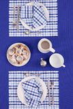 Laid table -  fork and spoon laid on blue cloth and white plate Stock Photo
