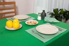 Laid table -  fork and spoon laid on green cloth and white plate Stock Photos