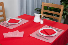 Laid table -  fork and spoon laid on red cloth and white plate Stock Images