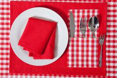 Laid table -  fork and spoon laid on red cloth and white plate Royalty Free Stock Image