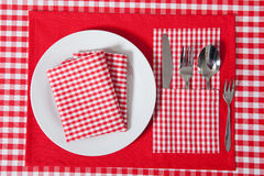 Laid table -  fork and spoon laid on red cloth and white plate Royalty Free Stock Photo