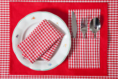 Laid table -  fork and spoon laid on red cloth and white plate Stock Photo