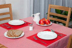 Laid table -  fork and spoon laid on red cloth and white plate Royalty Free Stock Images