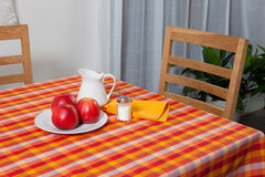 Laid table - fork and spoon laid on yellow, red and orange cloth. Fork and spoon laid on yellow, red and orange cloth in the kitchen, plate with appels stock photos