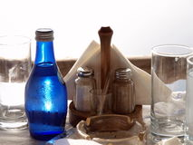 Laid table place settings. Details of glasses, condiments and blue bottle of water on table place setting stock images
