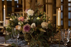 Laid Table By wedding banquet in a barn. Close-up. Laid Table By wedding banquet in a wooden barn. Candles and bouquet. Vintage Style. Close-up Stock Photography