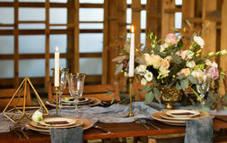 Laid Table by wedding banquet in a wooden barn. Stock Photos