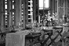 Laid Table By wedding banquet in a wooden barn. Candles and bouquet. Vintage Style. Black and white Stock Photo