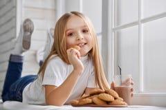 Laies lindos de la muchacha en travesaño de la ventana con las galletas y el chocolate caliente fotografía de archivo libre de regalías
