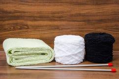 Laine, écharpe, et aiguilles de tricotage tricotées à l'arrière-plan en bois Image stock