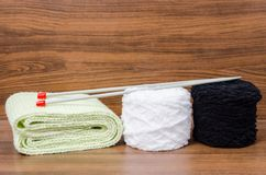 Laine, écharpe, et aiguilles de tricotage tricotées à l'arrière-plan en bois Photographie stock libre de droits