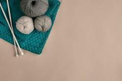 Laine de gris et de turquoise et aiguilles de tricotage de tricotage sur le fond beige Vue supérieure Copiez l'espace Photographie stock