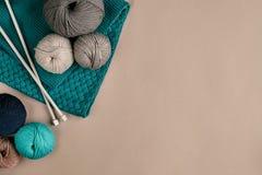 Laine de gris et de turquoise et aiguilles de tricotage de tricotage sur le fond beige Vue supérieure Copiez l'espace Images libres de droits