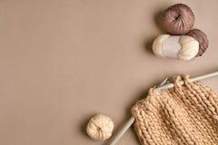 Laine de tricotage blanche et brune et tricotage sur des aiguilles de tricotage sur le fond beige Vue supérieure Copiez l'espace Photographie stock libre de droits
