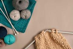 Laine de tricotage de gris et de turquoise et tricotage sur des aiguilles de tricotage sur le fond beige Vue supérieure Copiez l' Photos libres de droits