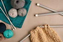 Laine de tricotage de gris et de turquoise et tricotage sur des aiguilles de tricotage sur le fond beige Vue supérieure Copiez l' Images libres de droits