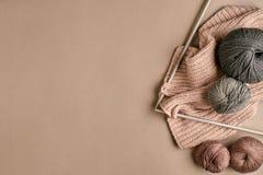 Laine de tricotage grise et brune et tricotage sur des aiguilles de tricotage sur le fond beige Vue supérieure Copiez l'espace Images libres de droits