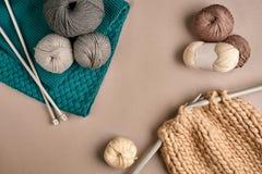 Laine de tricotage grise et brune et tricotage sur des aiguilles de tricotage sur le fond beige Vue supérieure Copiez l'espace Photographie stock libre de droits
