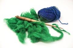 Laine verte, fil bleu et vieux plan rapproché d'axe sur le fond blanc Outils pour le tricotage de la laine Photographie stock libre de droits