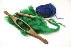 Laine verte, fil bleu et vieux plan rapproché d'axe sur le fond blanc Outils pour le tricotage de la laine Images libres de droits