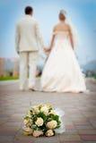 Laisser les couples nuptiales et le bouquet gauche de mariage Image libre de droits