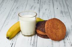 Lait, banane et biscuits sur une belle table en bois blanche Image libre de droits
