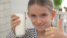 Lait boisson d'enfant au petit déjeuner dans la cuisine, fille goûtant des laitages images stock