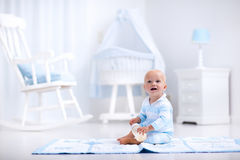 Lait boisson de bébé garçon dans la crèche ensoleillée Photo libre de droits