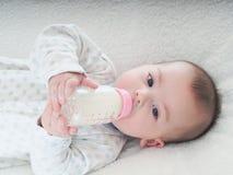 Lait boisson de bébé garçon de la bouteille à la maison Photo stock