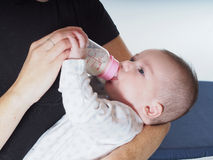 Lait boisson de bébé garçon de la bouteille à la maison Photographie stock libre de droits