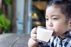 Lait boisson de fille et smartphone mignons asiatiques d'utilisation dans le café Images stock