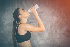 Lait boisson de jeune femme d'ajustement de la bouteille après exercice dans le gymnase Belle femme au gymnase faisant une pause photo stock