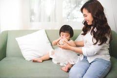 Lait boisson mignon de bébé à la maison avec sa maman Photos stock