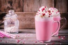 Lait chaud rose avec les coeurs fouettés de crème et de sucre dans une tasse en verre pour Valentine Day photographie stock