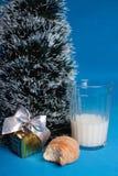 Lait, croissants, souvenir près d'arbre de Noël Photos stock