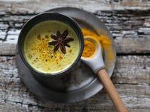 Lait d'or avec la poudre de safran des Indes dans le verre en céramique bleu sur un fond en bois, renforçant la santé et l'immuni image stock